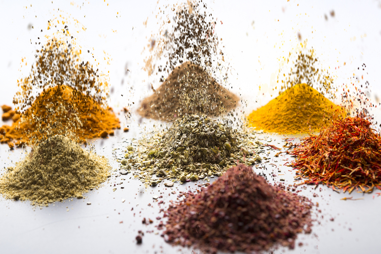 Different spices arranged on black reflective background